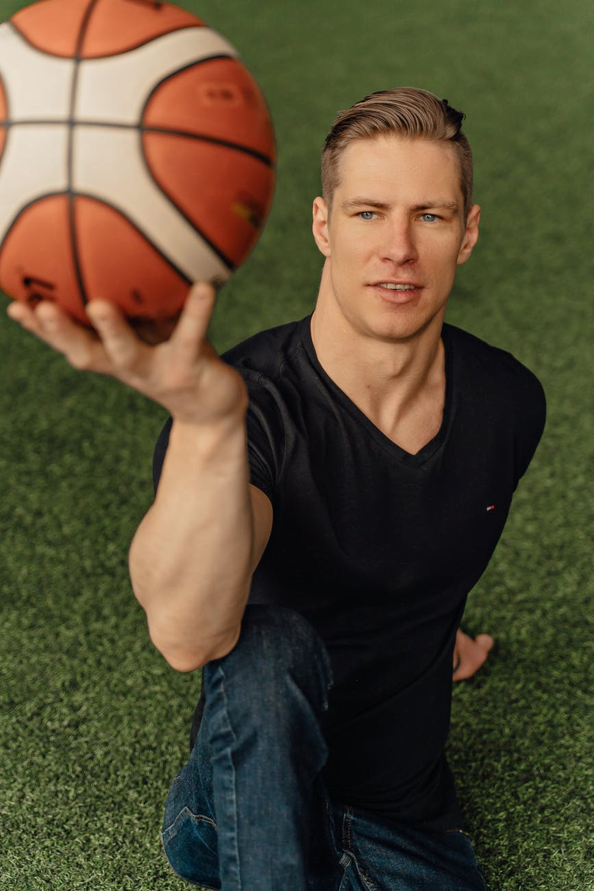 man in black v neck t shirt holding red basketball